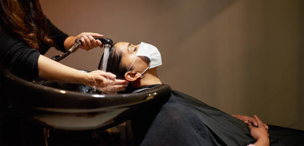 Woman wearing a face mask getting her hair washed in a salon stock photo