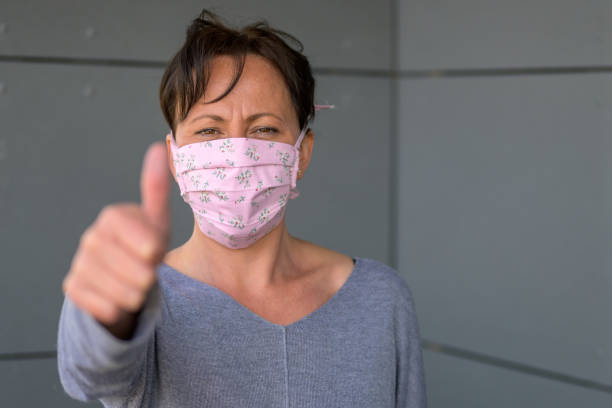 Woman wearing a face mask giving a thumbs up stock photo