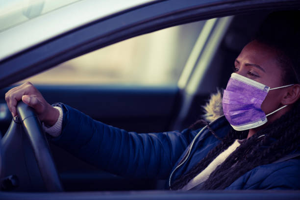 Woman wearing a face mask while driving a car. stock photo