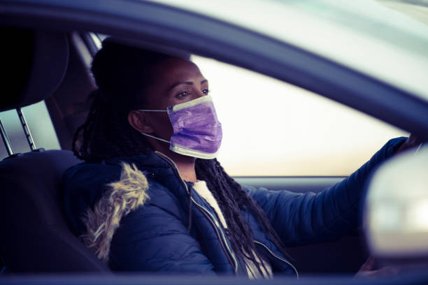 Woman wearing a face mask while driving a privet car. stock photo