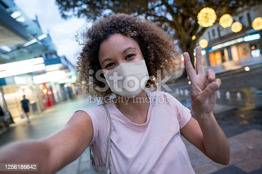 Portrait of an African American woman wearing a facemask and taking a selfie on the street making a peace sign during the COVID-19 pandemic