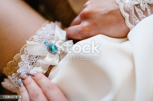Woman wearing a garter on the leg. The bride holds in hand garter in hotel room. morning preparation wedding concept.