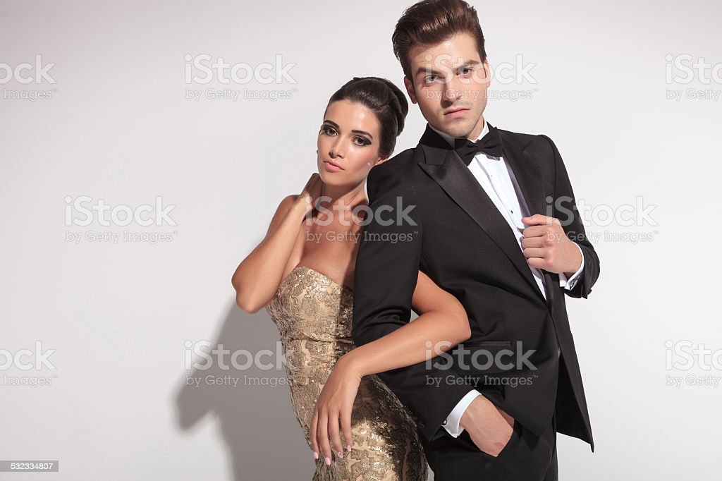 woman wearing a golden dress holding her man by arm stock photo