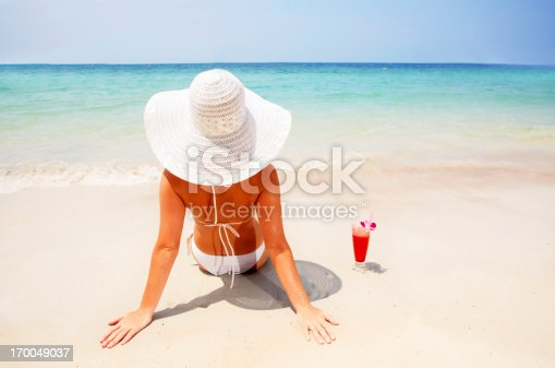 istock Woman wearing a hat relaxing on the beach. 170049037