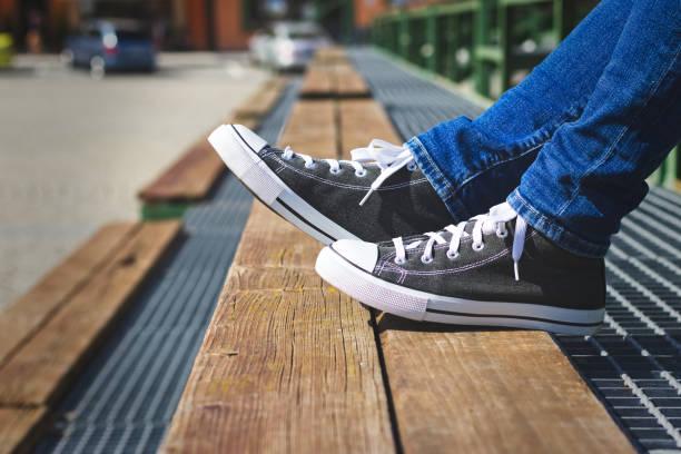 frau trägt eine jeans und canvas schuhe sitzen auf einer bank in der stadt - sitzbank schuhe stock-fotos und bilder