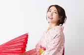 Woman wearing a kimono closing an umbrella
