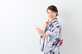 Woman wearing a kimono using a smartphone