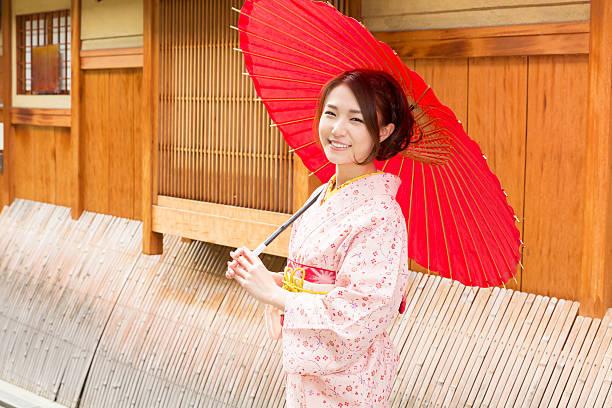 woman wearing a kimono with a red umbrella - kimono ストックフォトと画像