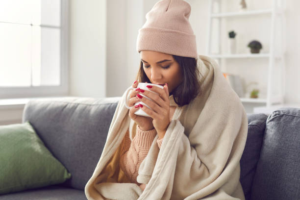 Woman wearing a knitted sweater and hat sitting on the sofa wrapped in a plaid drinking hot coffee. stock photo