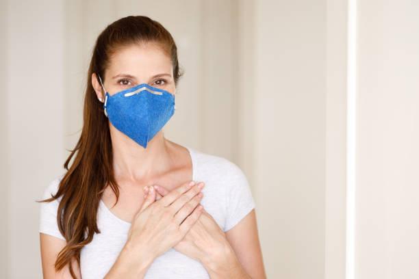 woman wearing a mask and doing social distance greeting - mão no peito imagens e fotografias de stock