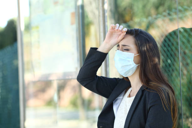 Woman wearing a mask complaining suffering head ache stock photo