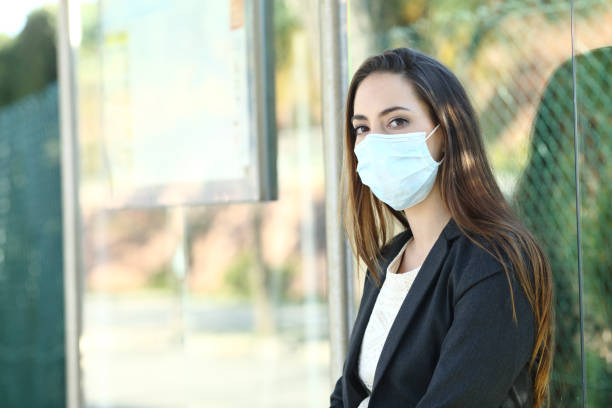 Woman wearing a mask to prevent contagion in a bus stop stock photo