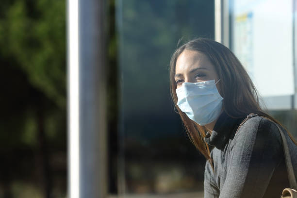 Woman wearing a mask waiting in a bus stop stock photo