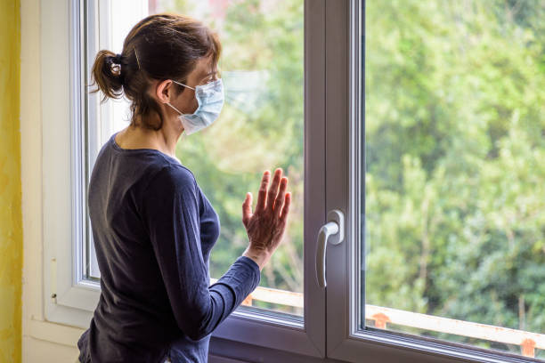 Une femme portant un masque médical de visage regarde dans l'espace par une fenêtre. - Photo