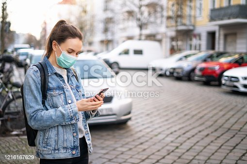 Woman wearing a protective surgical mask and using a smartphone on the city street