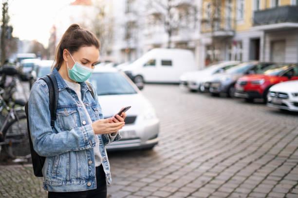 Frau trägt eine medizinische Maske und mit einem Telefon im Freien – Foto
