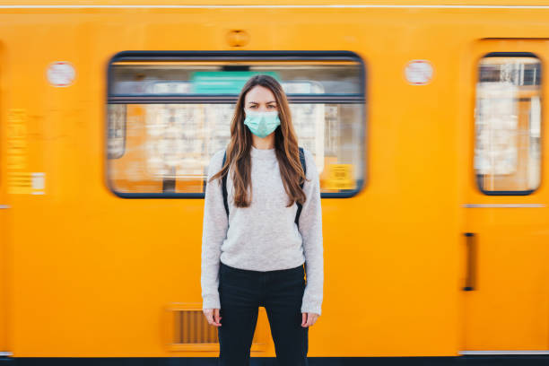 Frau trägt eine medizinische Maske in einer U-Bahn – Foto