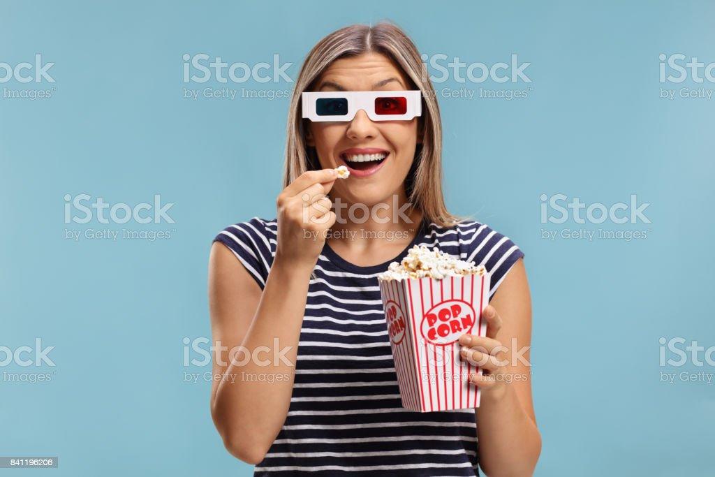 Femme portant une paire de lunettes 3D et manger des pop corn - Photo