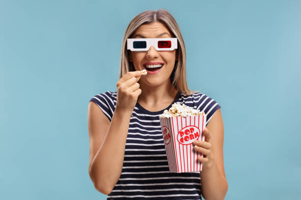 Woman wearing a pair of 3D glasses and eating popcorn stock photo