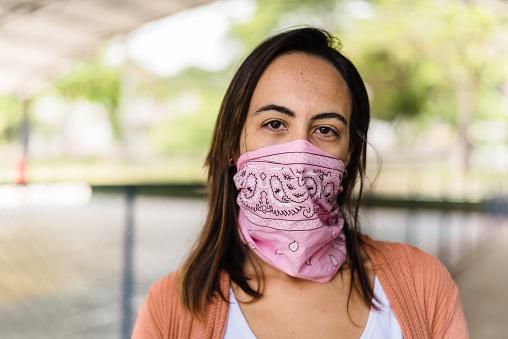 Woman wearing a pink headband as face mask