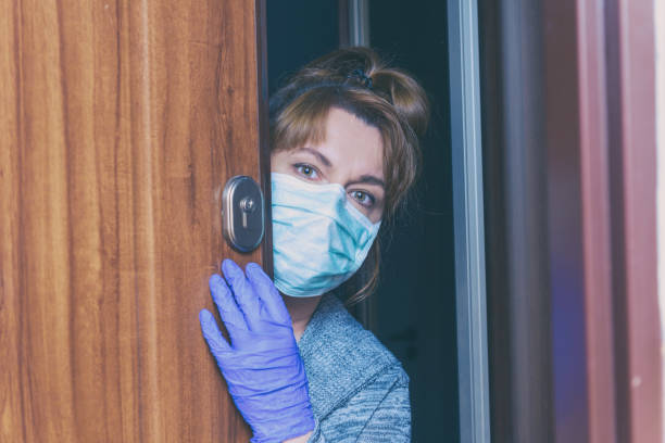 Woman wearing a protective face mask and gloves opening a door Woman wearing a protective face mask and gloves opening doors of her home because of an epidemic of corona virus covid-19. Home quarantine and self isolation concept stay at home order stock pictures, royalty-free photos & images