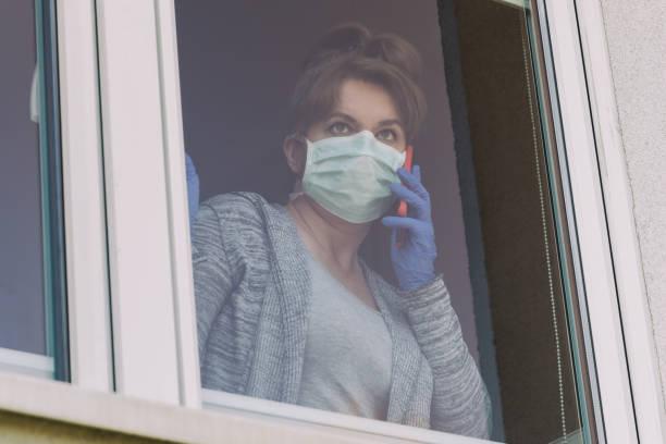 Frau trägt eine schützende Gesichtsmaske und schaut aus dem Fenster – Foto