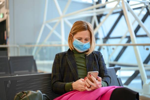 Frau trägt eine schützende Gesichtsmaske und mit einem Handy auf dem Flughafen Stock Foto – Foto