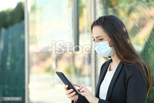 Woman wearing a protective mask using mobile phone sitting in a bus stop