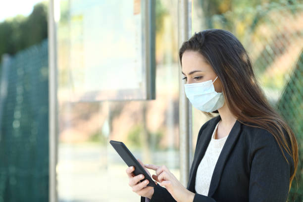Woman wearing a protective mask using phone stock photo