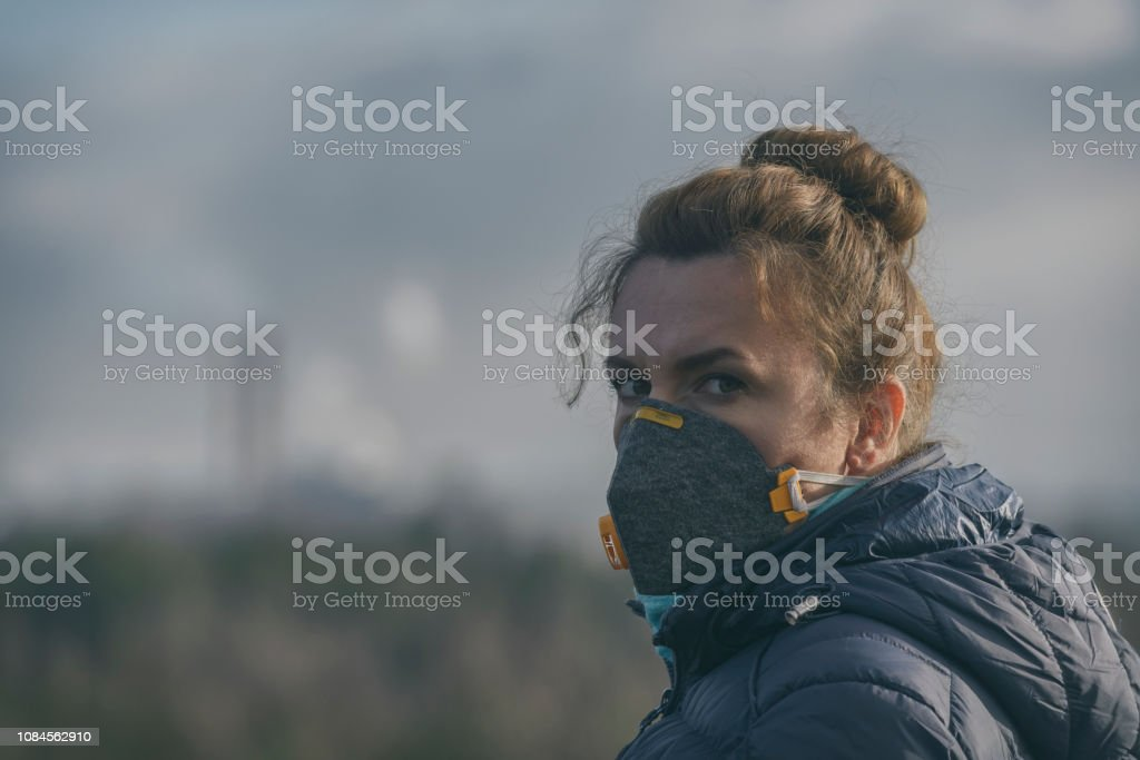 Woman wearing a real anti-pollution, anti-smog and viruses face mask stock photo