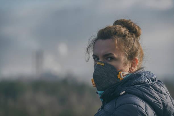 vrouw het dragen van een echte anti-vervuiling, anti-smog en virussen gezichtsmasker - smog stockfoto's en -beelden
