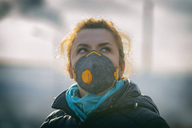 Woman wearing a real anti-pollution, anti-smog and viruses face mask Woman wearing a real anti-pollution, anti-smog and viruses face mask; dense smog in air. antipollution stock pictures, royalty-free photos & images