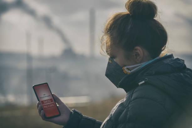 vrouw het dragen van een echte anti-smog gezichtsmasker en controleren van de huidige luchtvervuiling met smartphone app - smog stockfoto's en -beelden