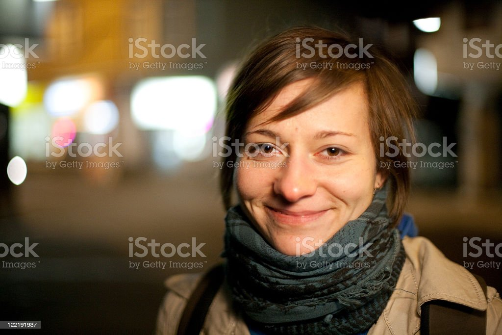 A woman wearing a scarf and a smile at night stock photo