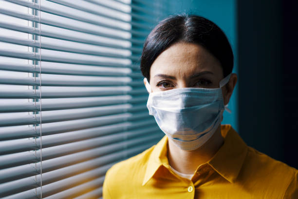 Woman wearing a surgical mask and looking at camera