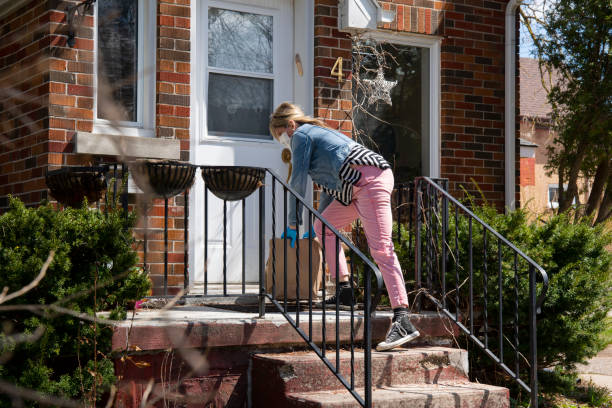 A woman wearing a surgical mask and protective gloves drops off bags of groceries onto the front steps of a small house. stock photo