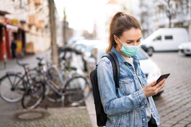 Frau trägt eine chirurgische Maske und mit einem Telefon im Freien – Foto