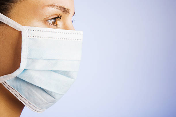 Woman wearing a surgical mask  surgical mask stock pictures, royalty-free photos & images
