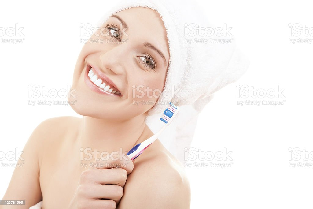 Woman wearing a towel brushing her teeth royalty-free stock photo