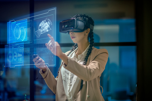 Female engineer wearing a virtual reality headset at work to explore an upcoming mechanical engineering project. She uses her hands to manipulate and explore the finer details.
