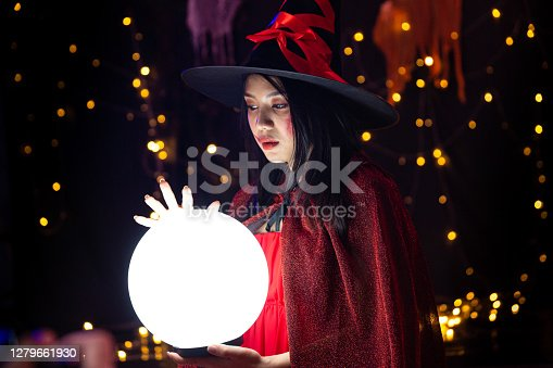 A woman wearing a witch costume and holding a crystal ball at Halloween. Halloween festival.