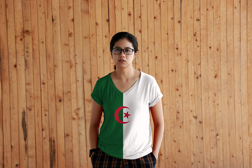 Woman wearing Algeria flag color shirt and standing with two hands in pant pockets on the wooden wall background, two equal vertical bars, green and white, charged in the center with a red star and crescent.