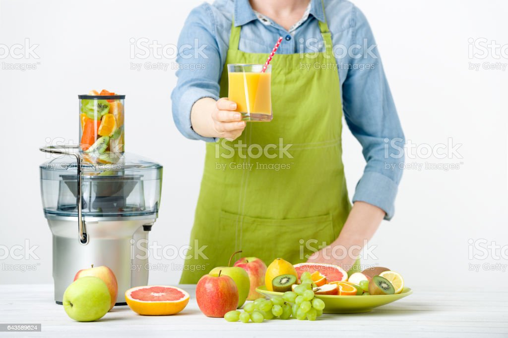 Woman wearing an apron, offering glass of freshly pressed juice – Foto
