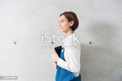 istock Woman wearing an apron with a tablet PC 1200949981