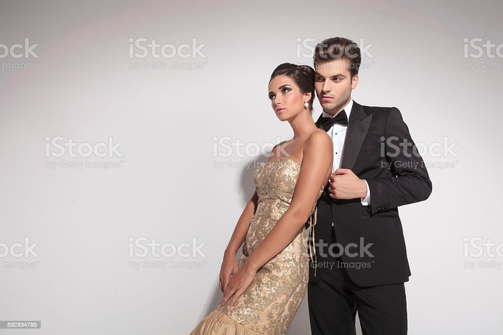 woman wearing an elegant dress leaning on her lover stock photo