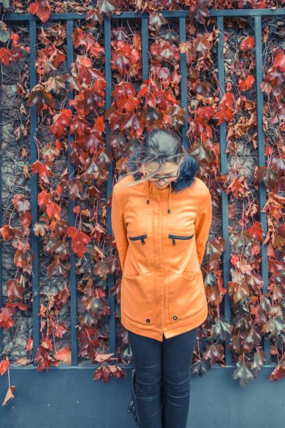 frau trägt eine orange jacke posing vor einem tor mit bunten herbstlaub - lederjacke mit kapuze damen stock-fotos und bilder