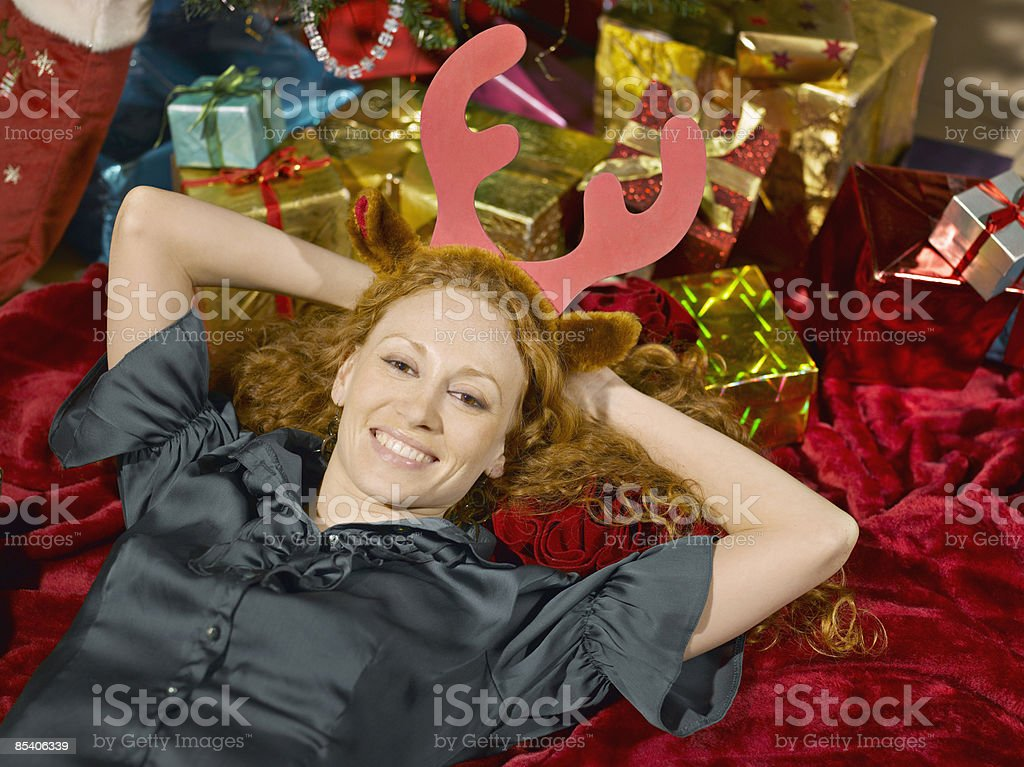 Woman wearing antlers laying near Christmas gifts royalty-free stock photo