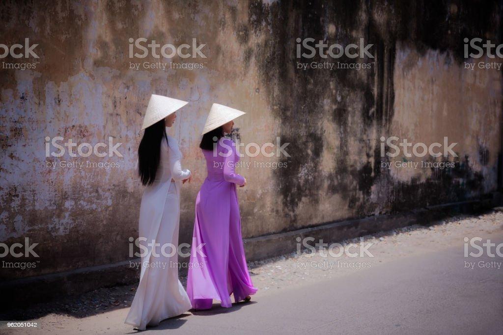 Frau trägt Ao Dai Kultur traditionell auf lokalen Straße laufen. – Foto