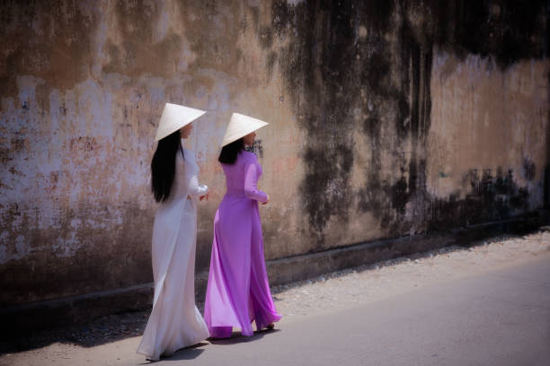 woman wearing ao dai culture traditional walking on local street. - ao dai stock photos and pictures