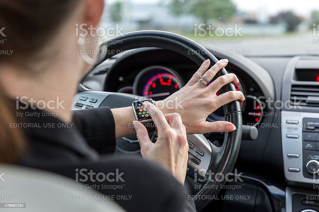 Woman wearing Apple Watch while driving a car stock photo